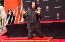 Keanu Reeves plasma huellas y firma en Hollywood